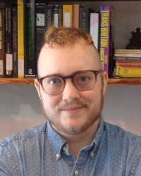 A person with short brown hair, a beard, and glasses, shown from the shoulders up. They are wearing a polka-dot blue shirt and are standing in front of a bookshelf.