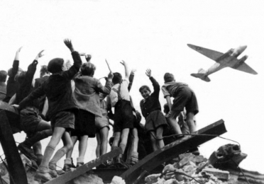 Children waving at a plane during the Berlin Airlift