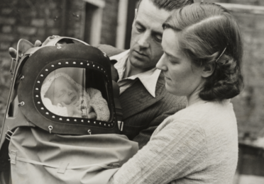 Young couple holding their baby in a protective container
