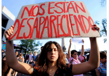"""Protestor carrying a sign that reads """"We are made to disappear"""""""