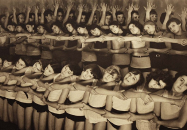 Still from black and white film showing row of children linking arms