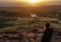 Isabel Martin standing on top of Arthur's Seat at sunrise