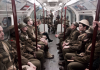 actors and artists performing world war soldiers riding London subway